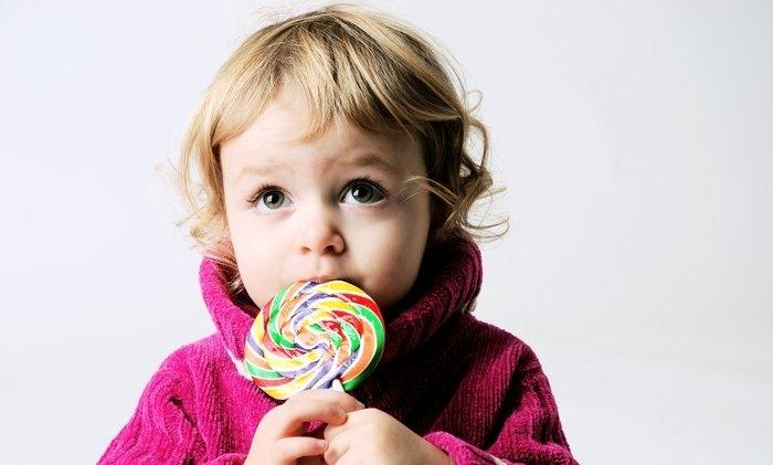 Девочка с конфетой на палочке