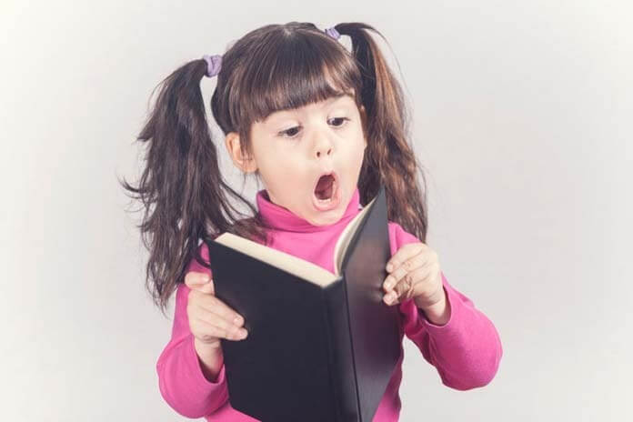 Little girl reacts while reading a book